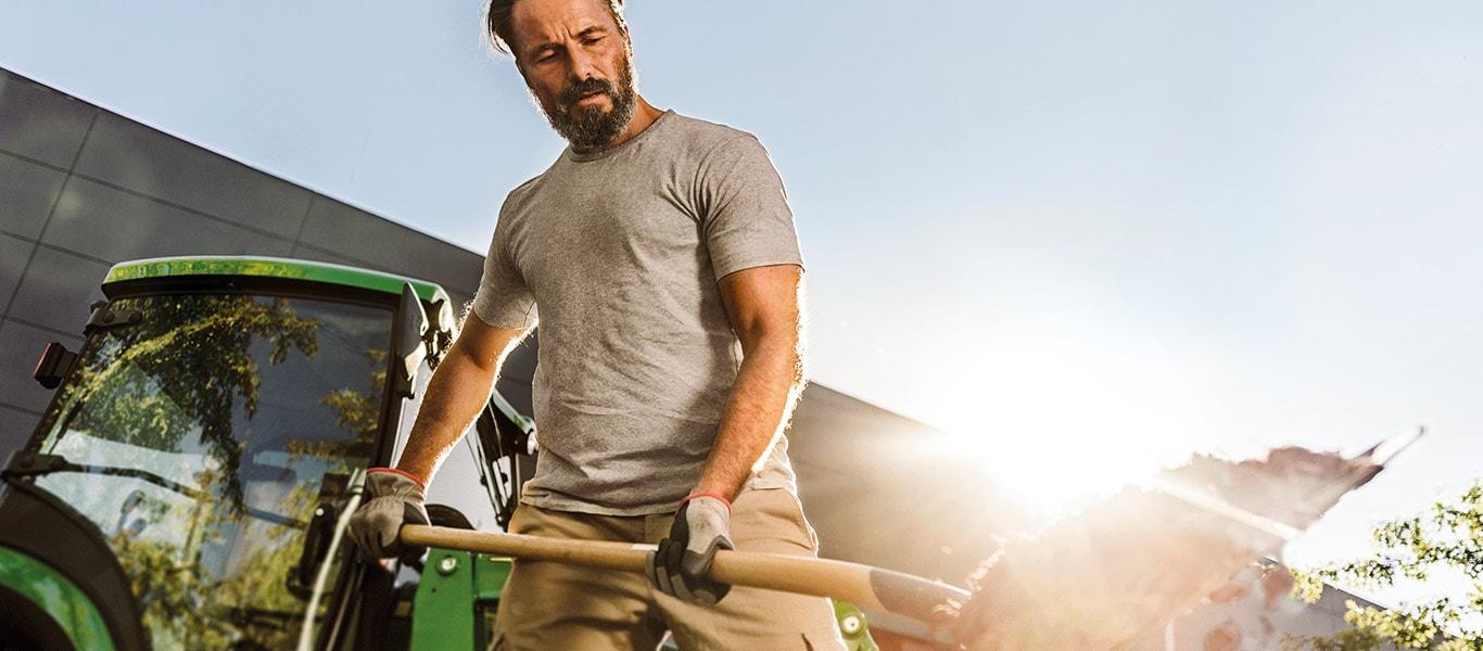 Hombre trabajando en un tractor utilitario compacto